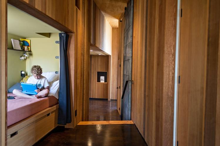 Max Bacon, 8, in the home designed by Mary and Ray Johnston for his parents, David and Lisa. The house is a one-bedroom that sleeps 11 because of a number of such alcoves and hidden spaces.