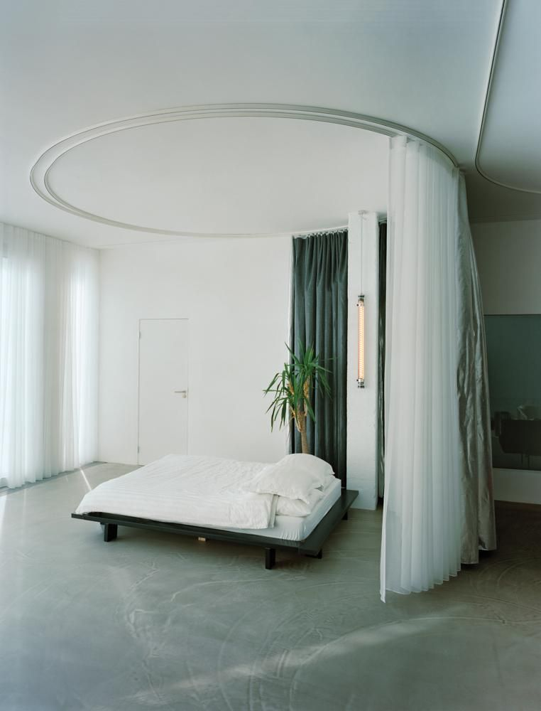MATERIAL WORLD Two draperies, translucent and opaque, encircle the bed.