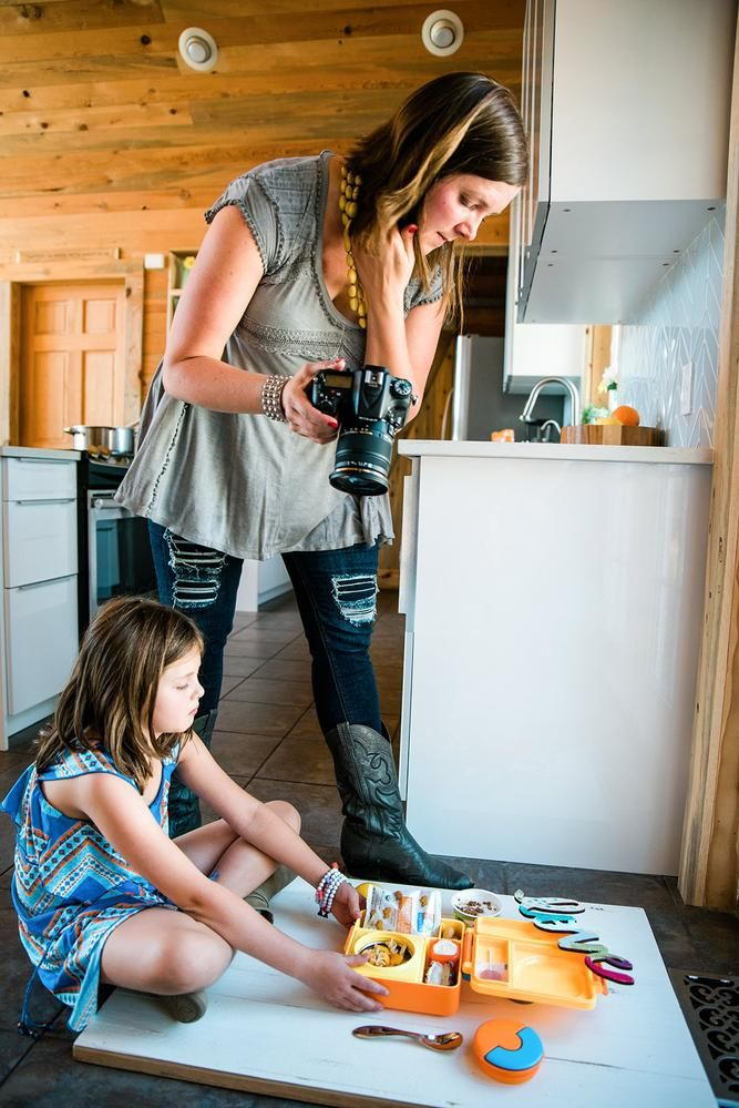 Kelly Pfeiffer, assisted by her daughter Kaela, photographs a school lunch for her Nosh and Nourish blog and Instagram account.