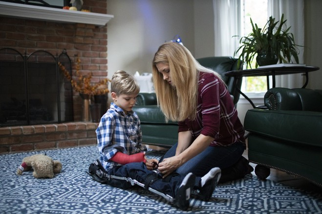 Christa Bottomley helps her son, Sebastian, put on leg braces. Ms. Bottomley says thousands of hours of rehabilitation and nerve-transfer surgeries have enabled her son to be able to walk with a walker and braces.