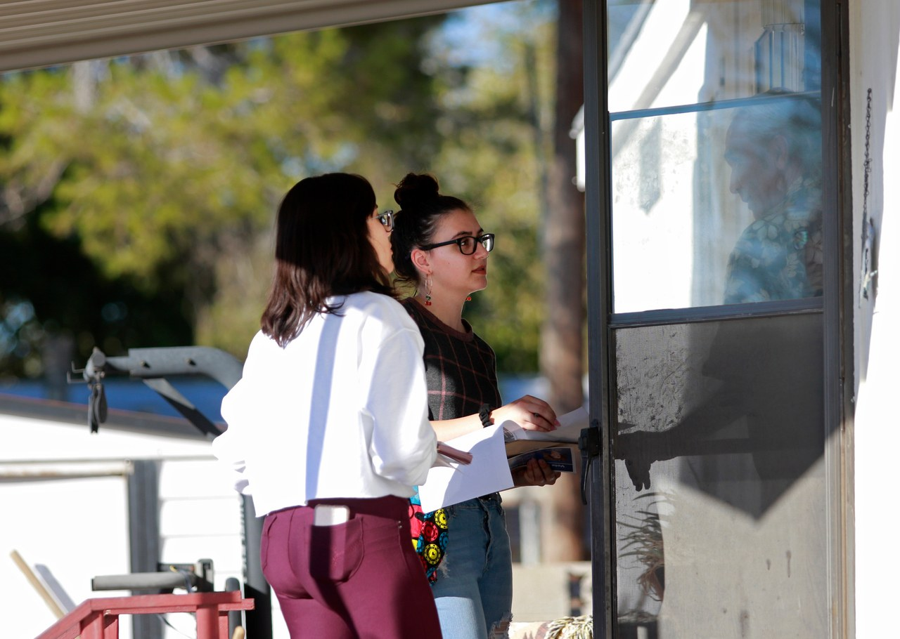 Students Katherine Nieto, 15, left and Jocelyn Hoffman, 19, right canvass a neighborhood Thursday, Oct. 23, 2018, in Las Vegas. (Photo by Ronda Churchill for Glamour)