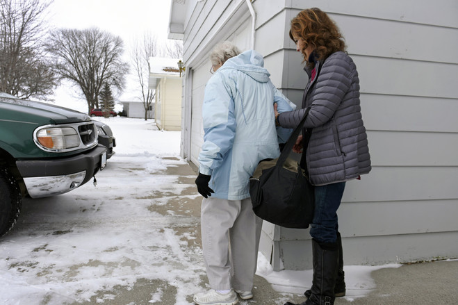 Ms. Moris guides Mrs. Jaster to her car for their weekly trip to Grand Forks. The volunteers with Faith in Action help older adults in Pembina County with transportation, light housework and meals.