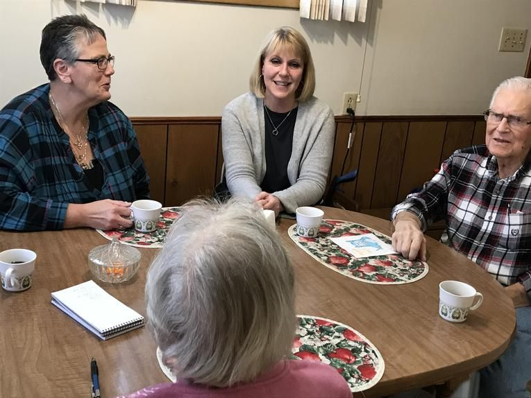 The Jasters talk at their kitchen table with Michelle Murray, head of Faith in Action, far left, and the youngest of their three children, Holly Giesbrecht, who travels from her home in Canada on Thursdays to help out.