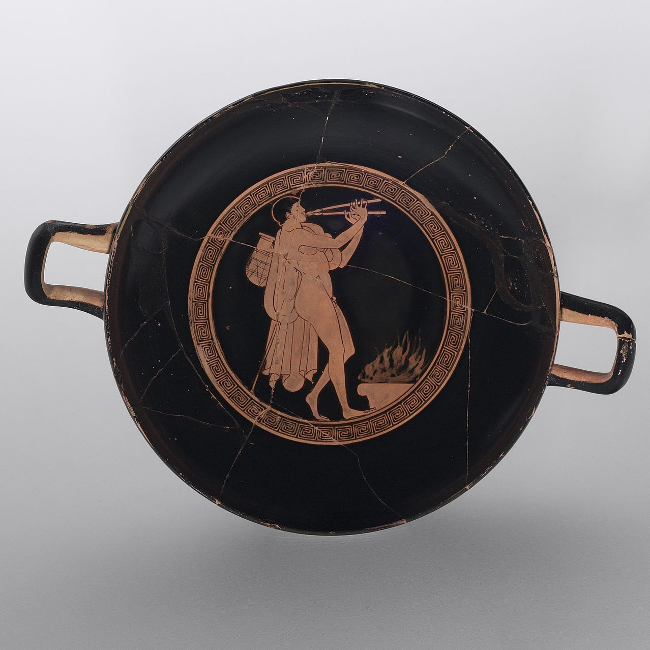 A Greek kylix with a man playing an aulos (double-reed instrument) at an altar (c. 480–470 B.C.), attributed to the Brygos Painter