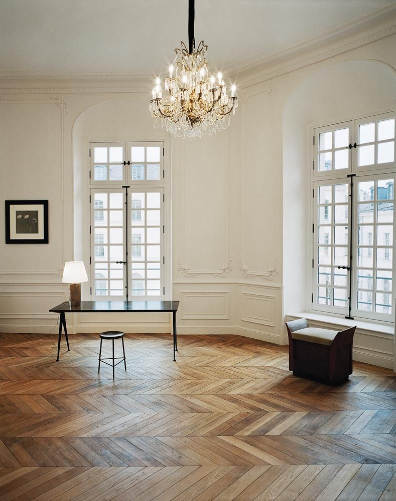 """A room featuring a Jean Prouvé table and a Pierre Jeanneret stool, next to a 1982 photograph by Robert Mapplethorpe. """"We wanted to leave behind [the former headquarters at] Avenue George V and position the Saint Laurent brand somewhere more elevated and chic,"""" says Vaccarello."""