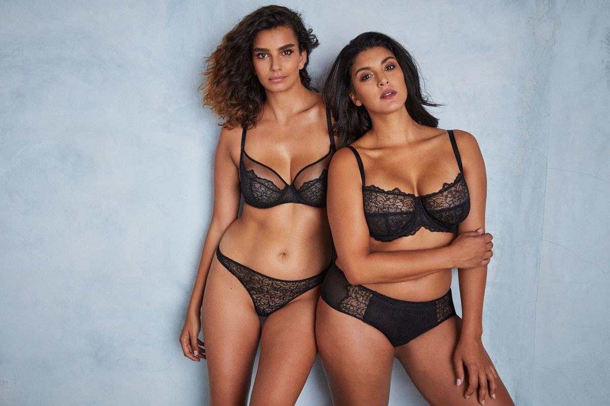 Two women model black lace bras and panties from Liberte's first collection
