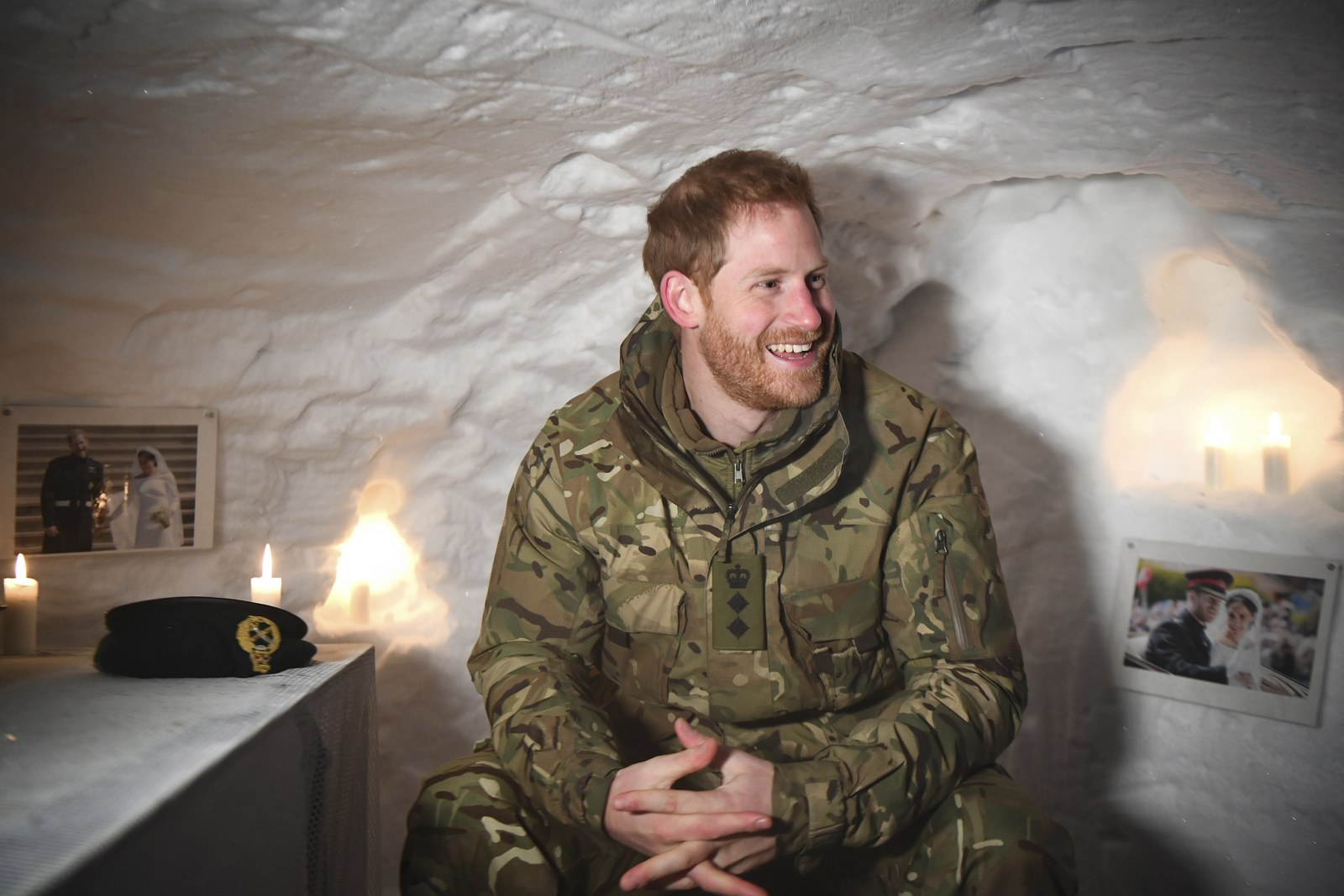 Prince Harry in a makeshift shelter built of snow covered in pics of Meghan Markle.