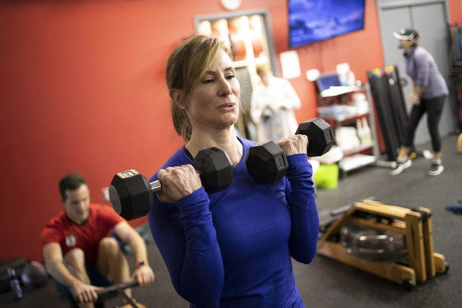 Ms. Kichline lifts weights during a group fitness class at Purenergy studio.