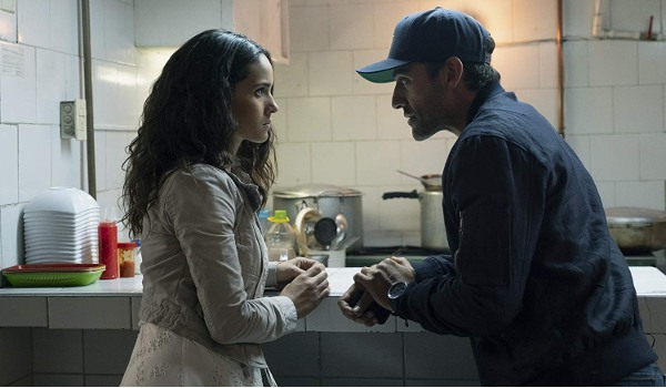 Triple Frontier Adria Arjona and Oscar Isaac speaking in secret at a food counter