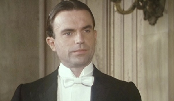 Reilly Ace of Spies Sam Neill dressed in a white tie tuxedo, half smiling in a parlor