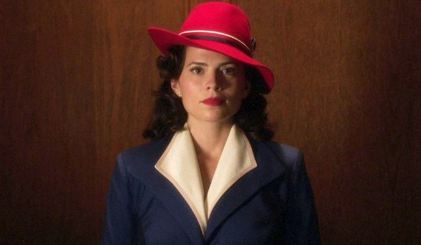 Agent Carter Hayley Atwell in a blue jacket and red hat, riding the elevator