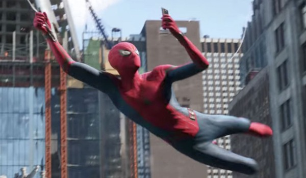 Spider-Man: Far From Home Peter checking his phone in costume as he swings around New York