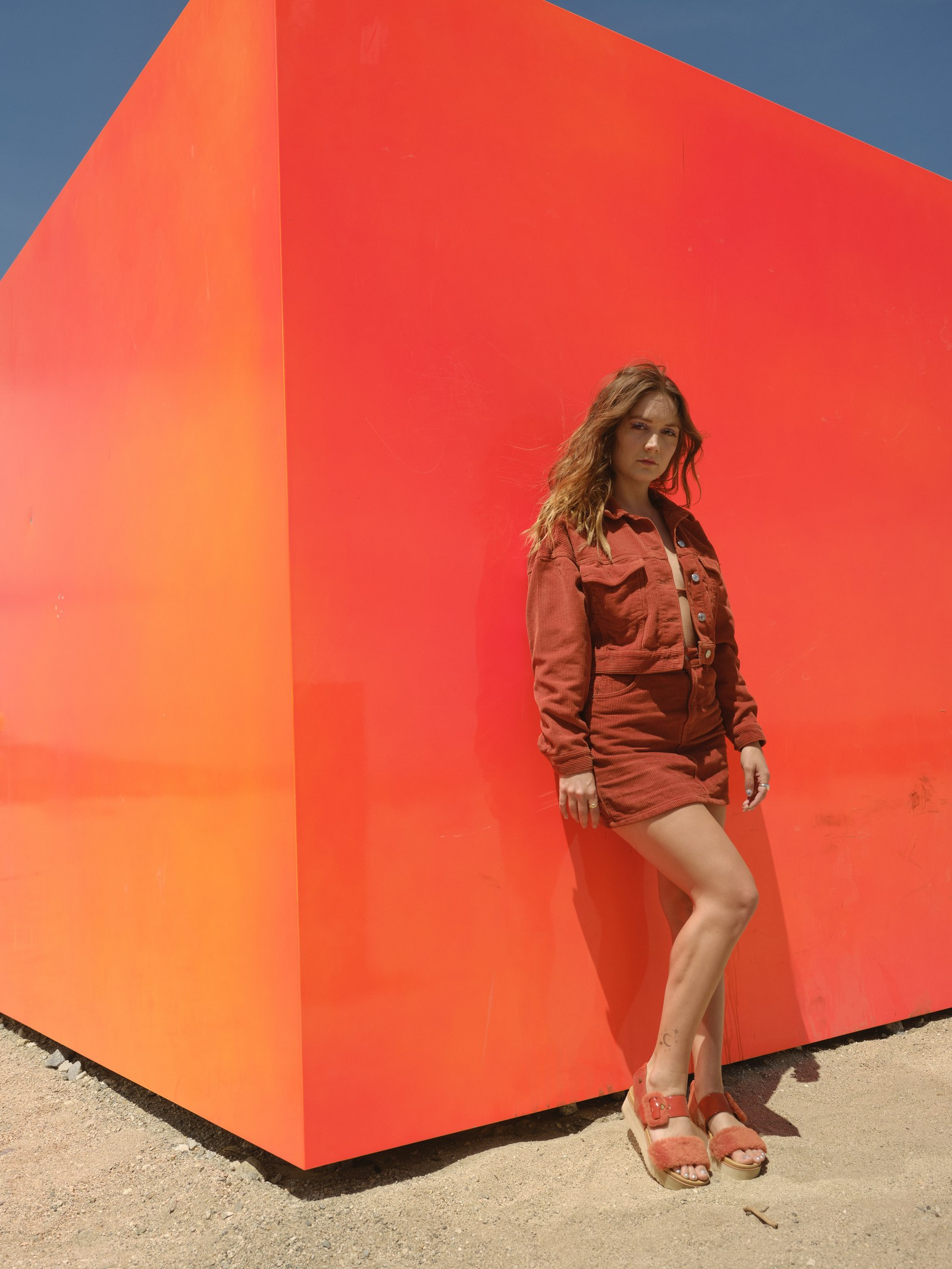 woman standing in front of an orange cube