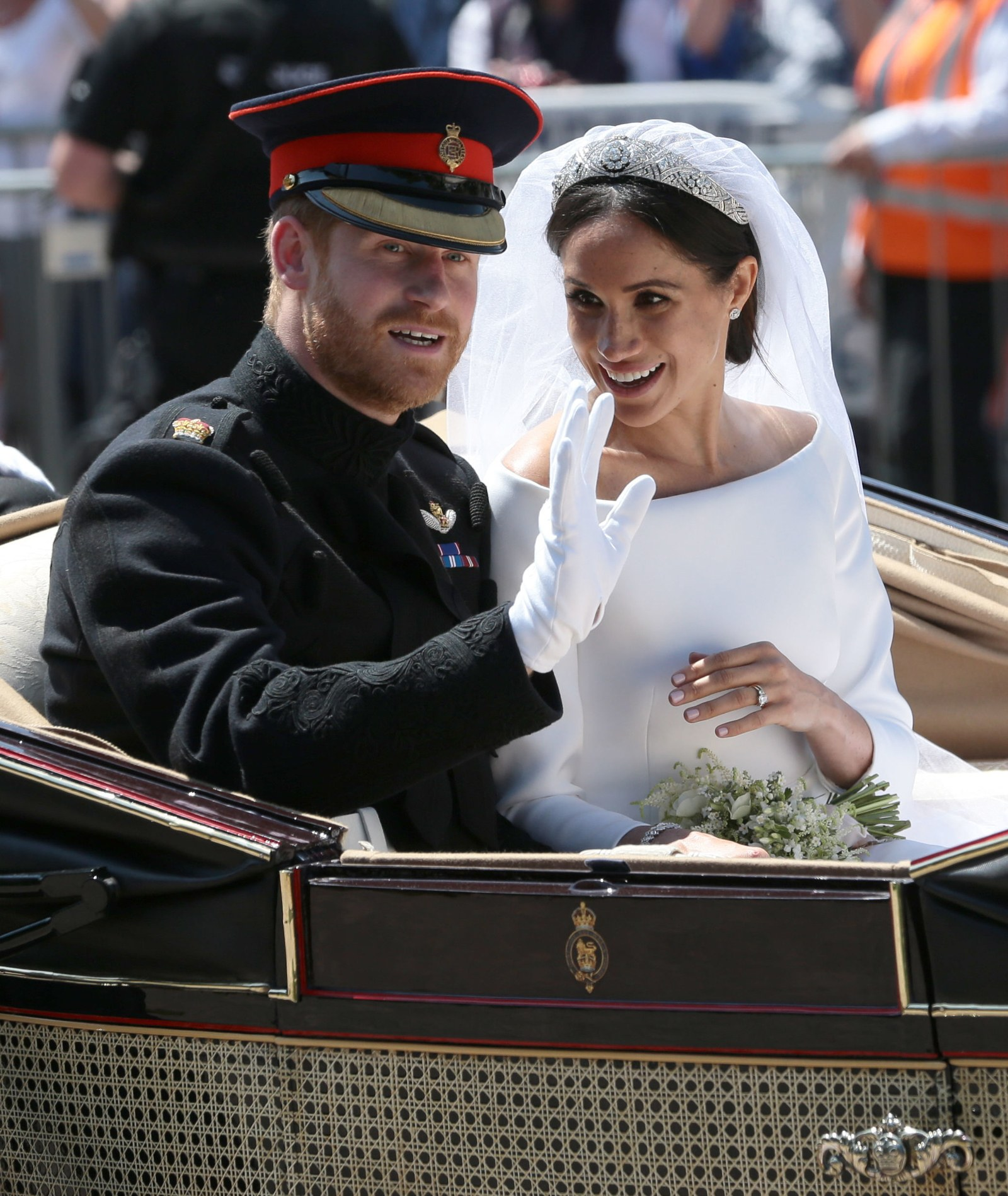 Prince Harry Duke of Sussex and Meghan Duchess of Sussex wave from the Ascot Landau Carriage during their carriage...