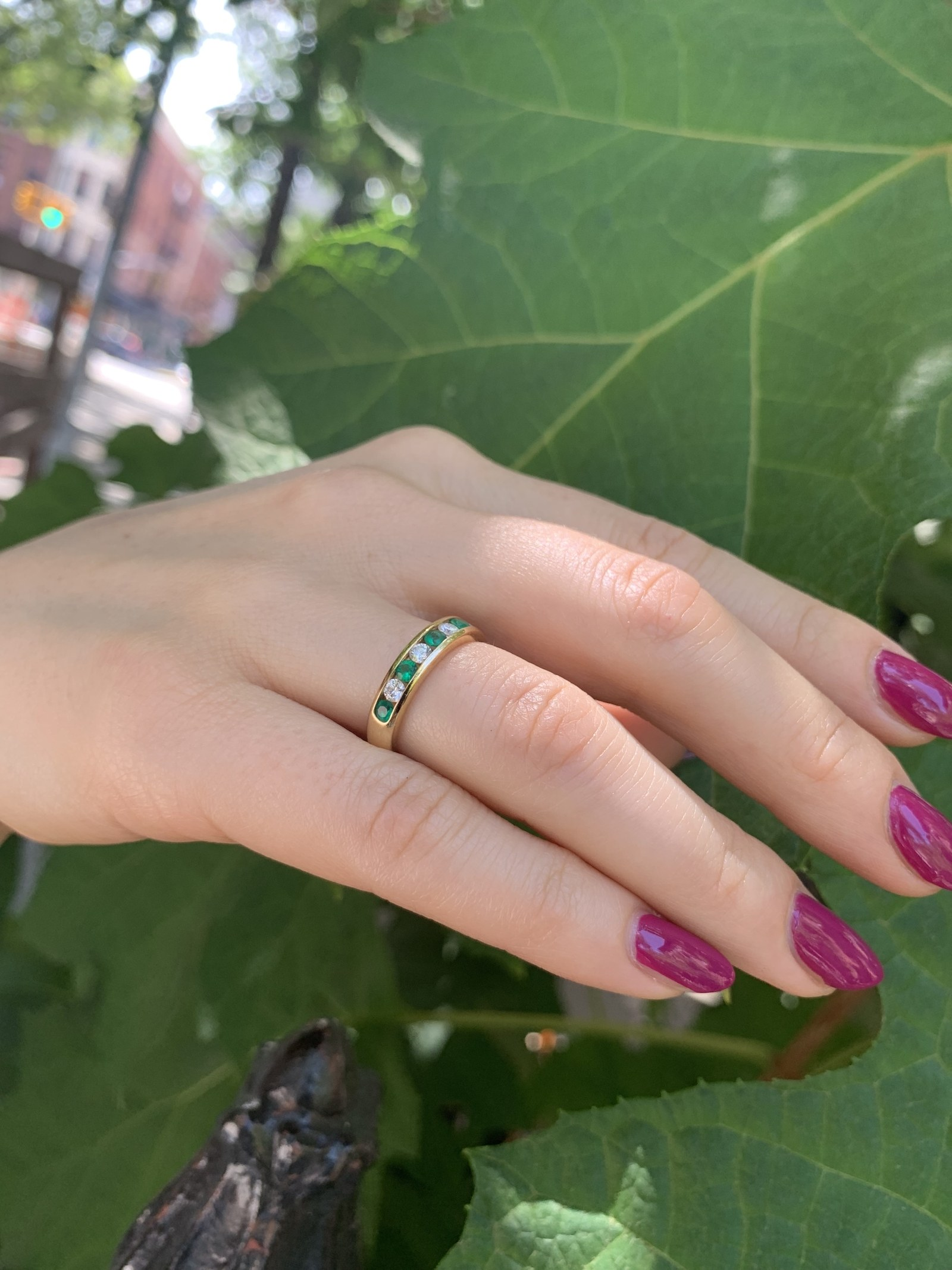 Woman's hand with diamond and emerald ring.