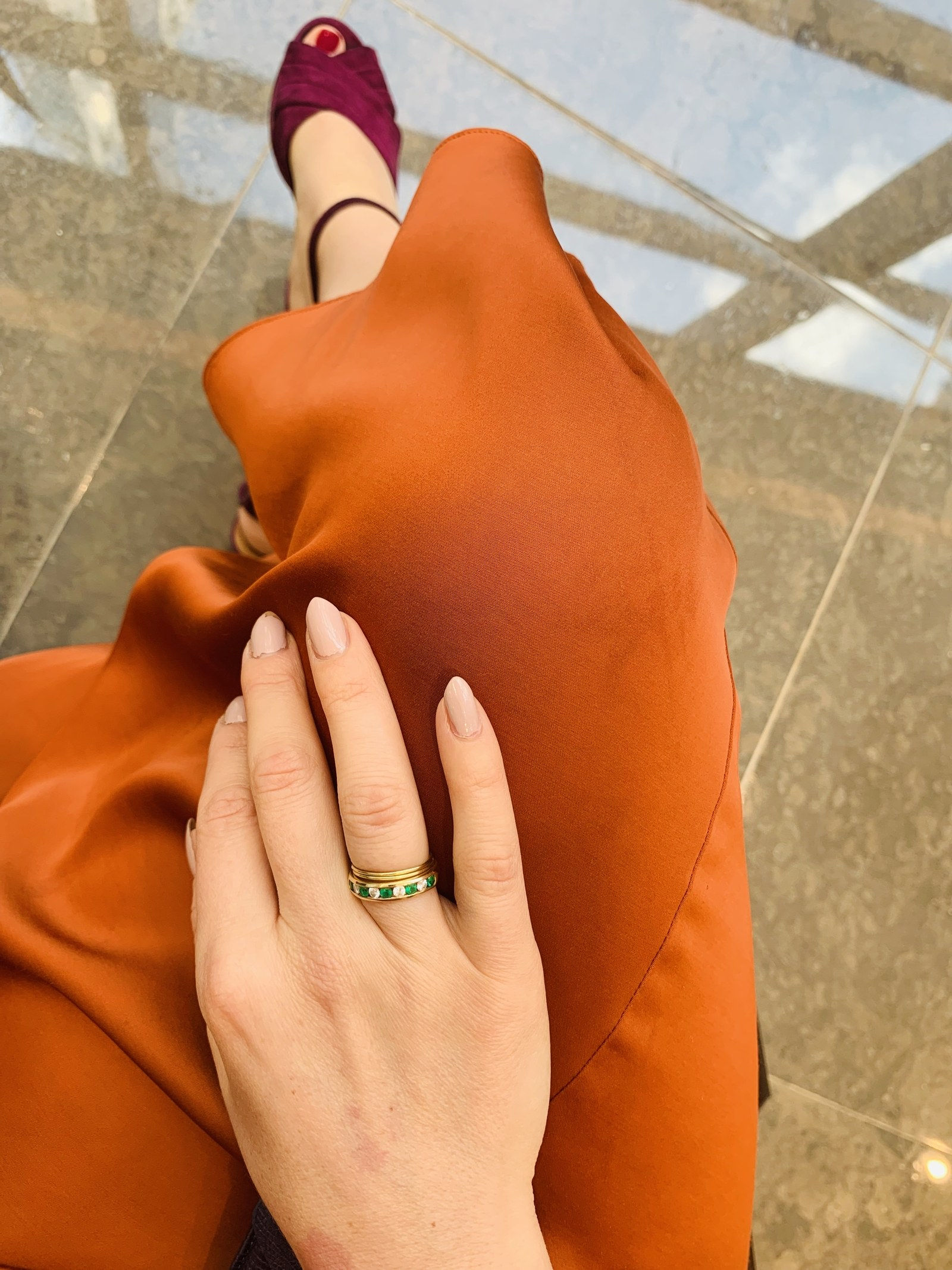 Photo of woman's hand with emerald and diamond ring.