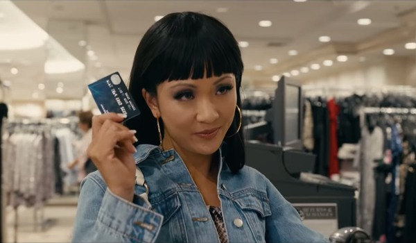 Hustlers Constance Wu flashing a credit card at the mall, with a smile