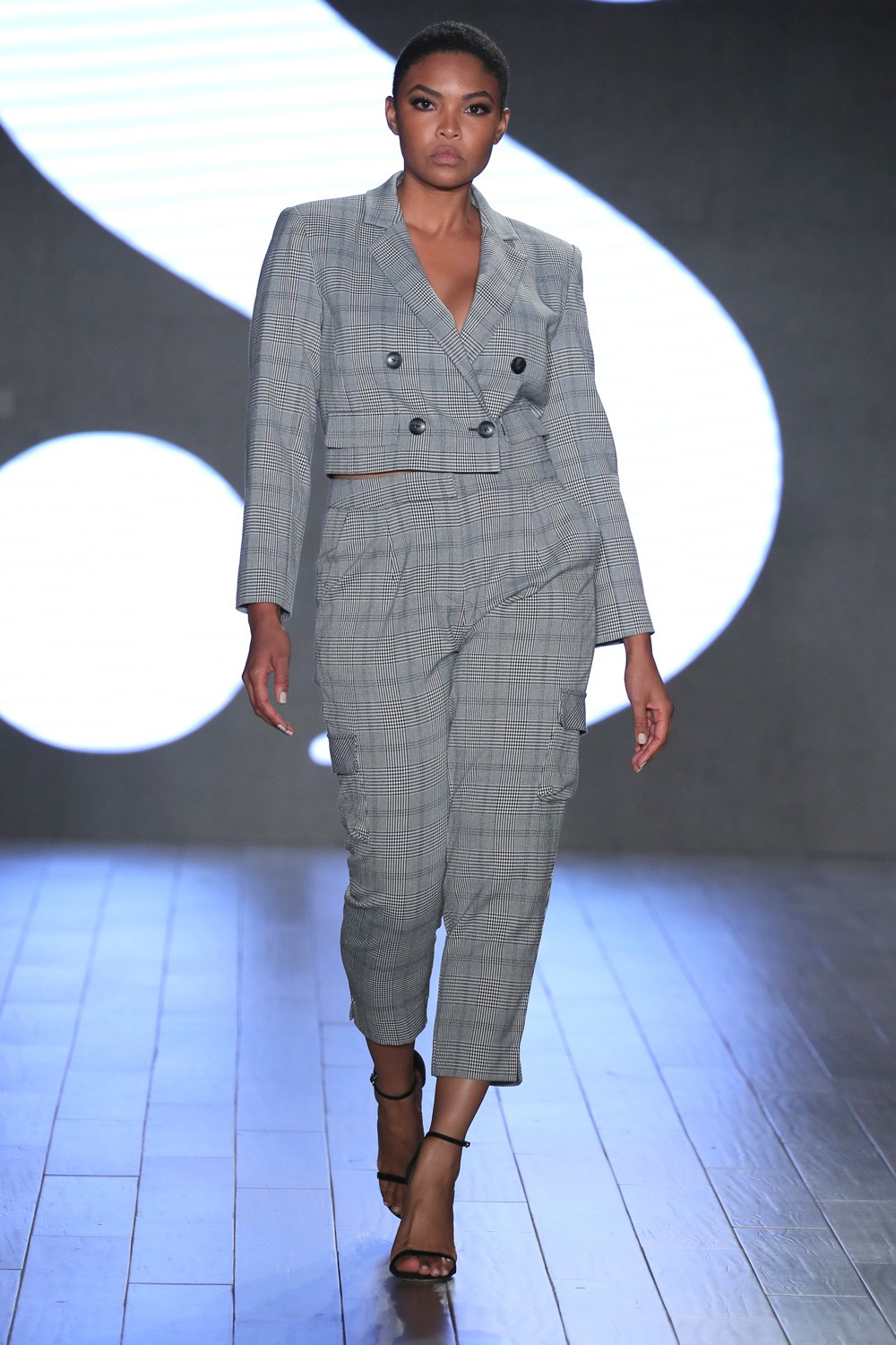 a model wearing a checked suit on the runway