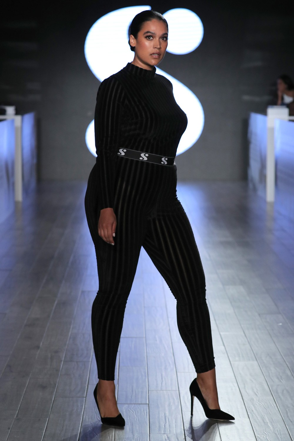 woman wearing a black catsuit on the runway
