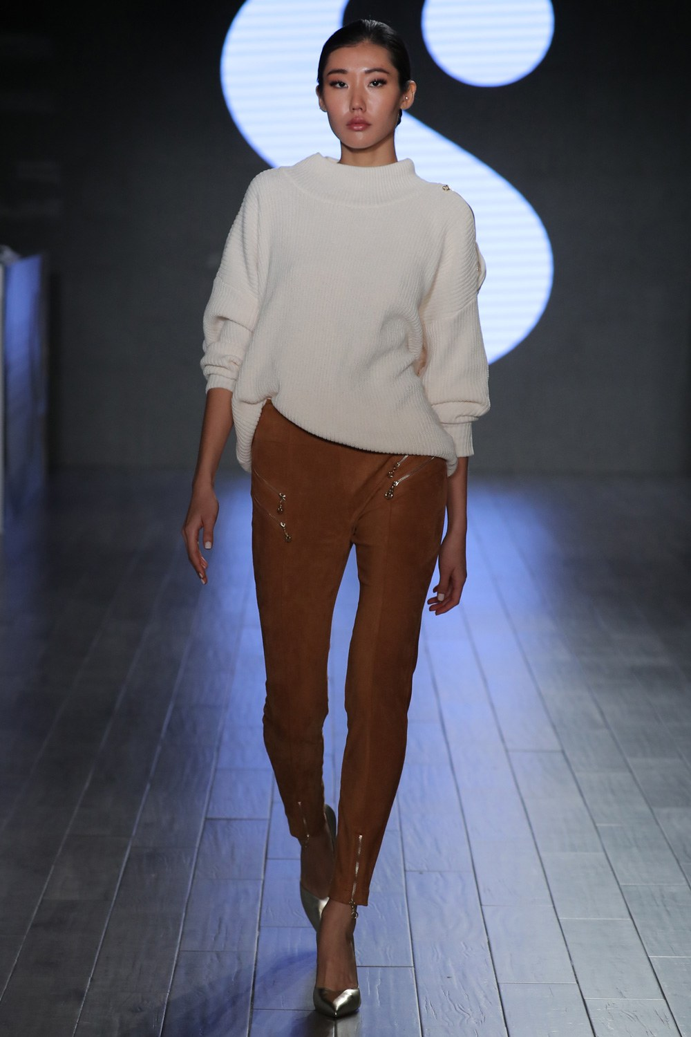 model on the runway wearing leggings and a sweater