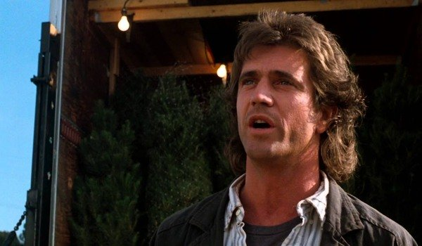 Lethal Weapon Mel Gibson talking in front of a truck of Christmas trees
