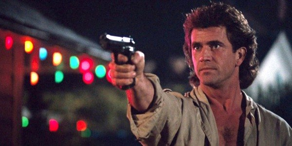 Lethal Weapon Mel Gibson aims a gun next to some Christmas lights