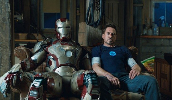 Iron Man 3 Tony sitting on a couch, next to his armor