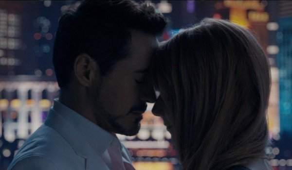 Iron Man 3 Tony and Pepper getting close in front of a skyline