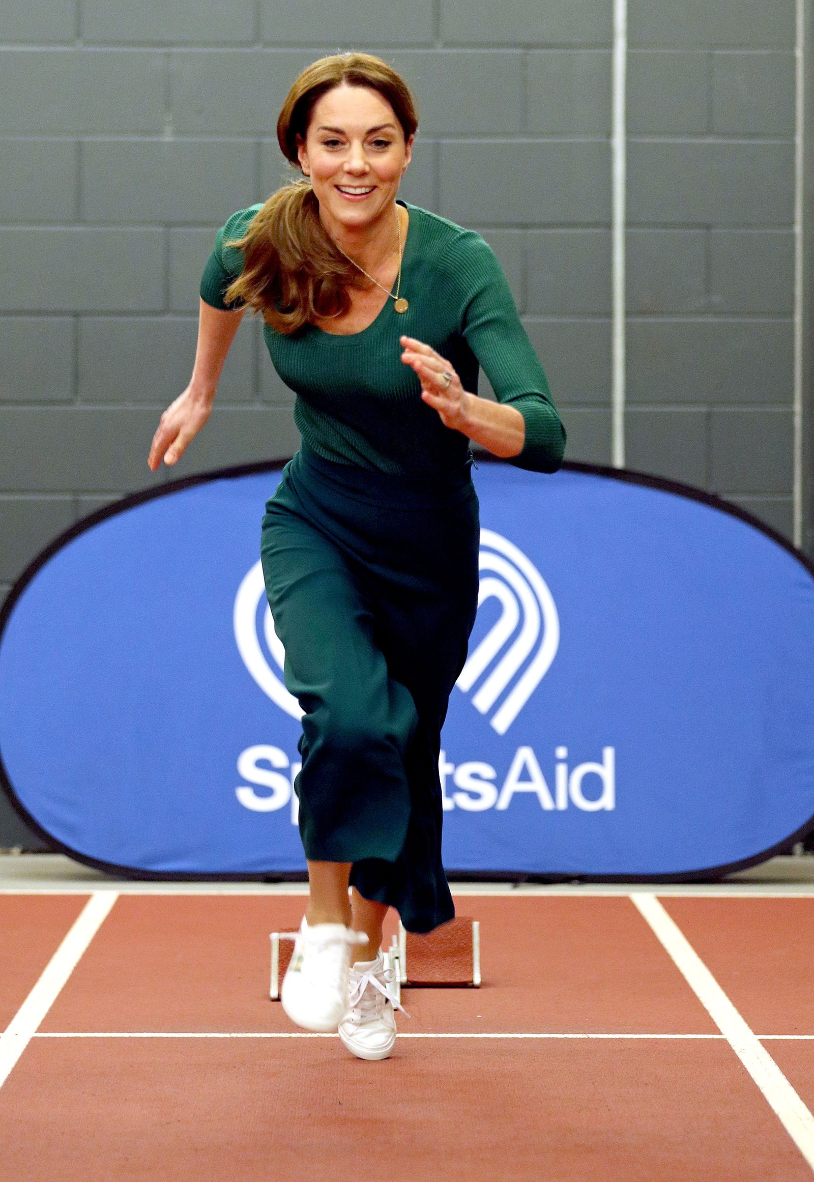 Britain's Catherine Duchess of Cambridge tries out the running track with starting blocks during a SportsAid event at...