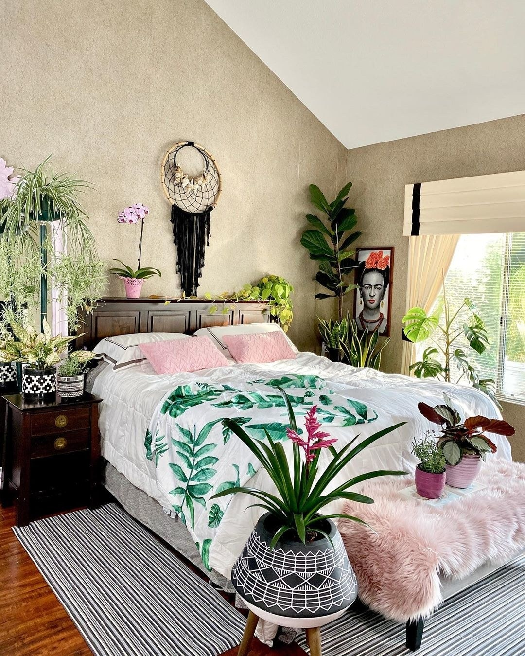 bedroom with colorful comforter and plants