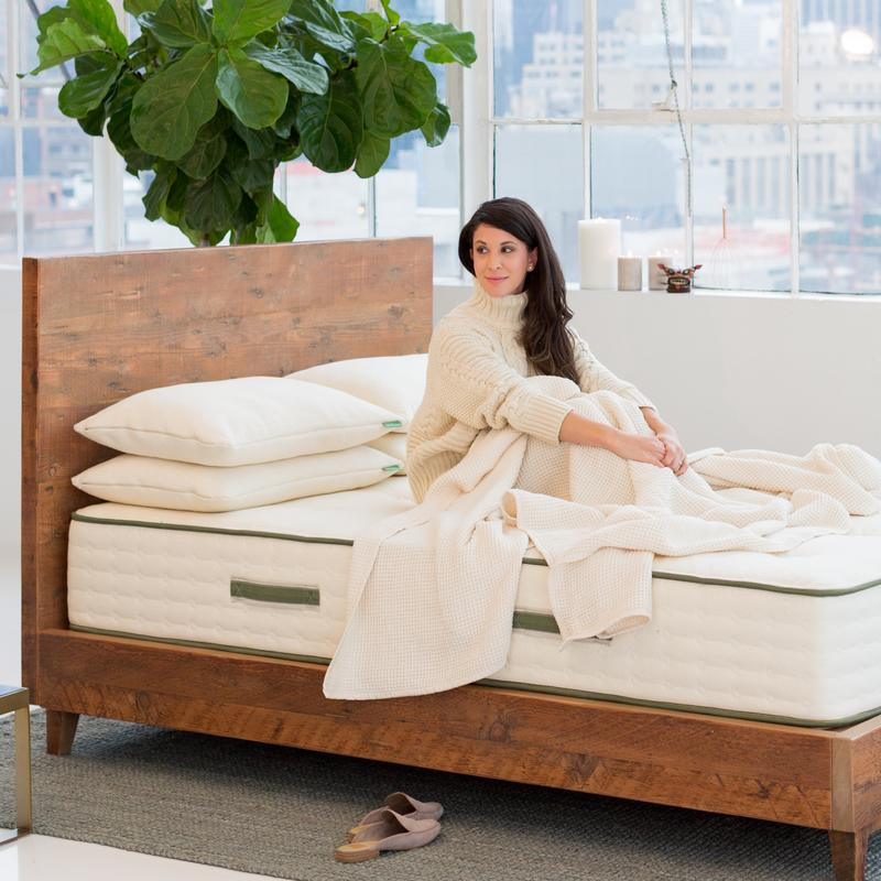 woman sitting on avocado green mattress on wood bed frame with blanket and pillow