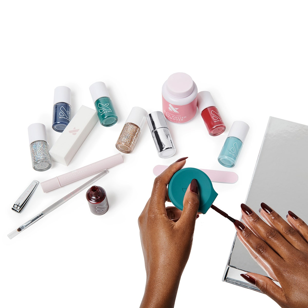 olive & june mani system hands applying nail polish with nail polish, nail file, polish remover and brushes