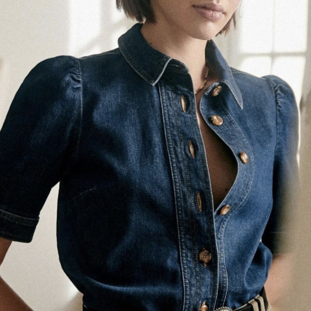 model wearing denim short sleeve button up shirt