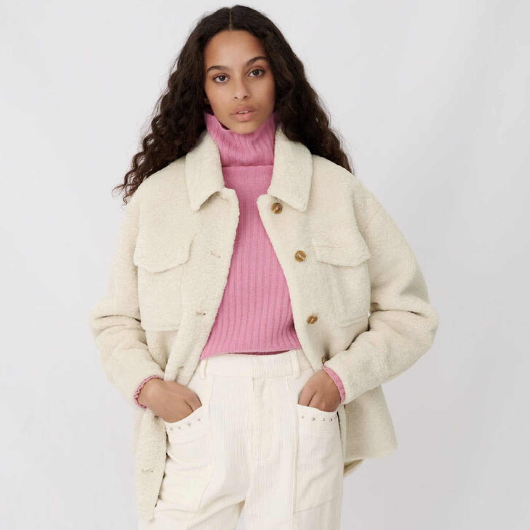 model wearing white fuzzy jacket over pink turtleneck with white pants