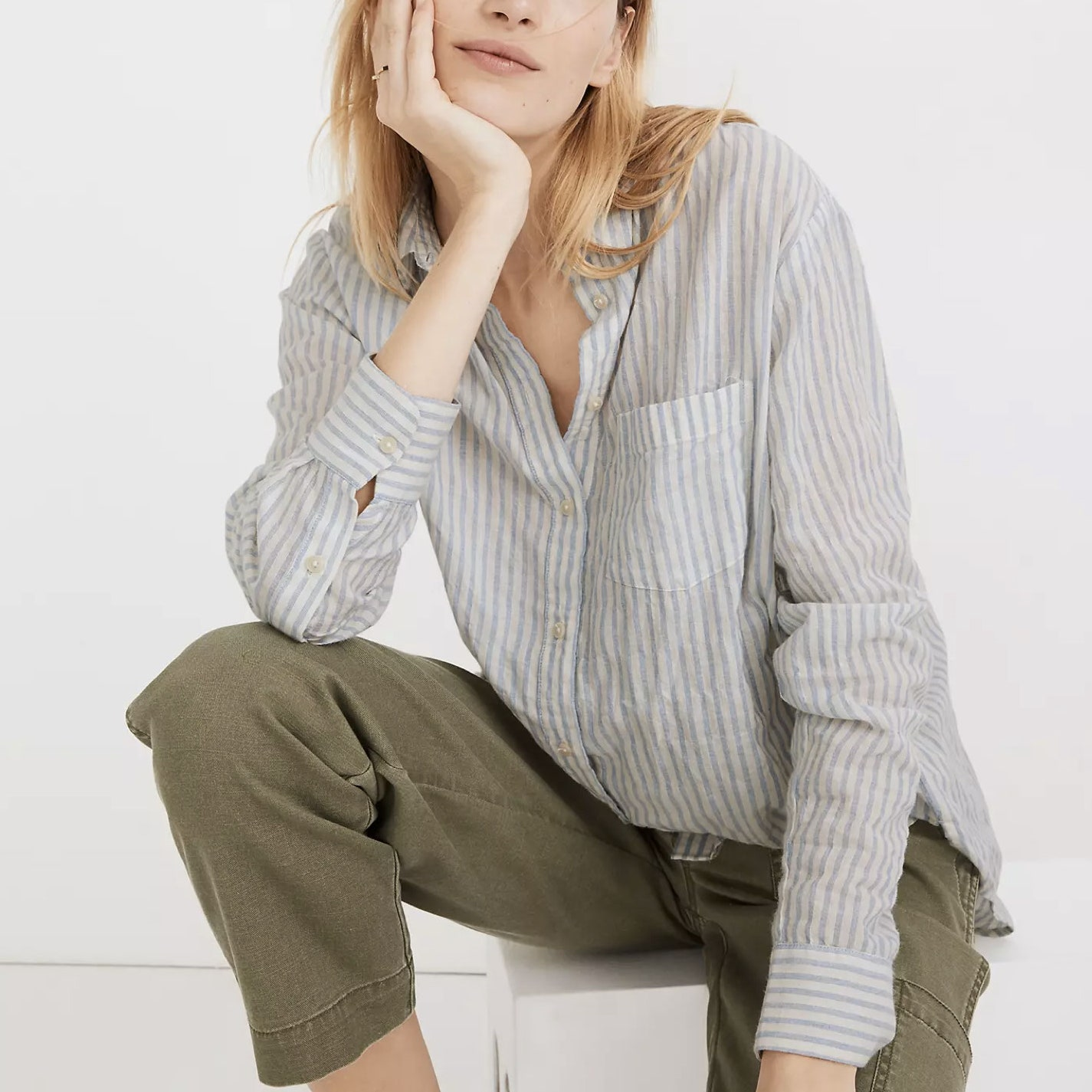model wearing light blue and white striped button down shirt