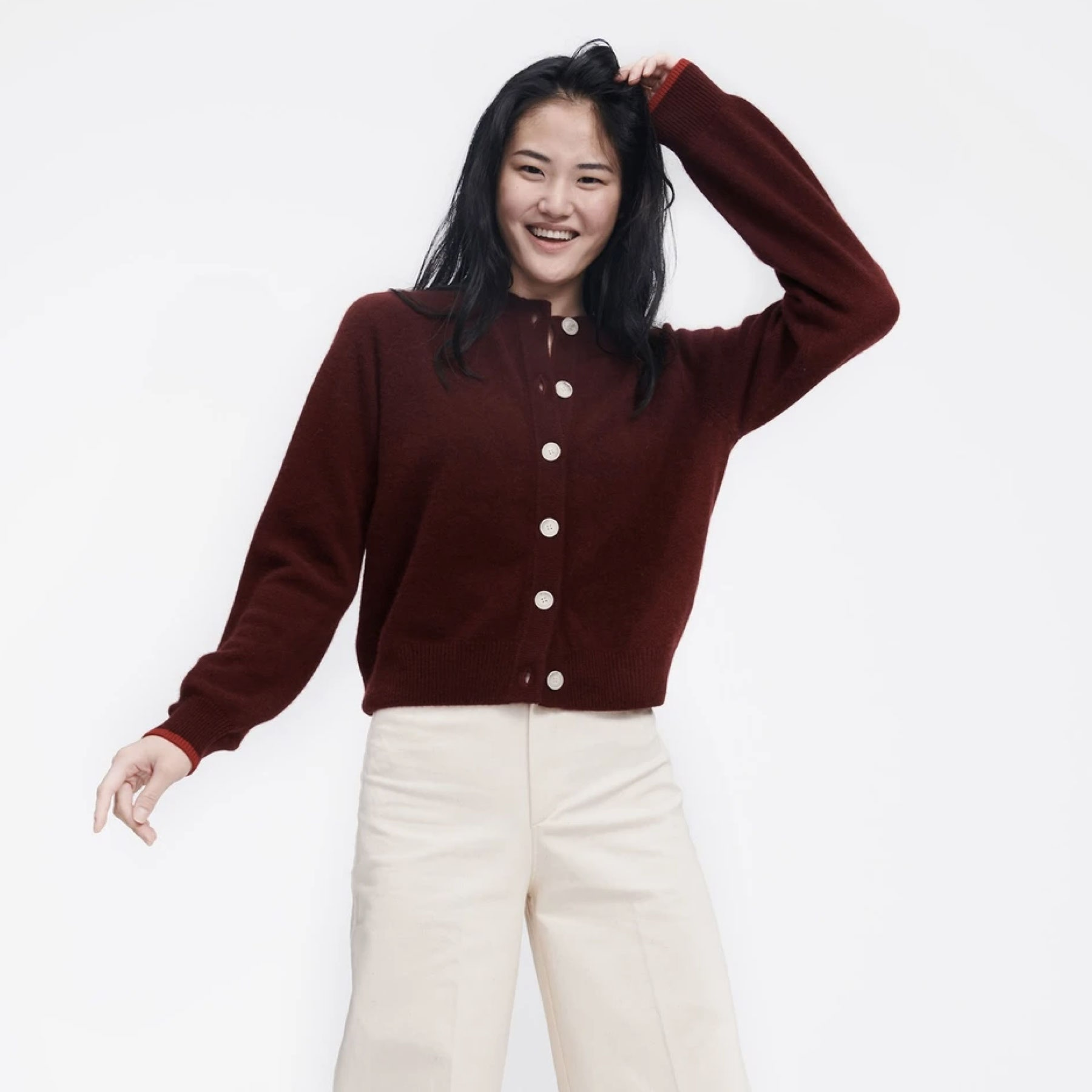 model wearing red sweater with white buttons and white pants