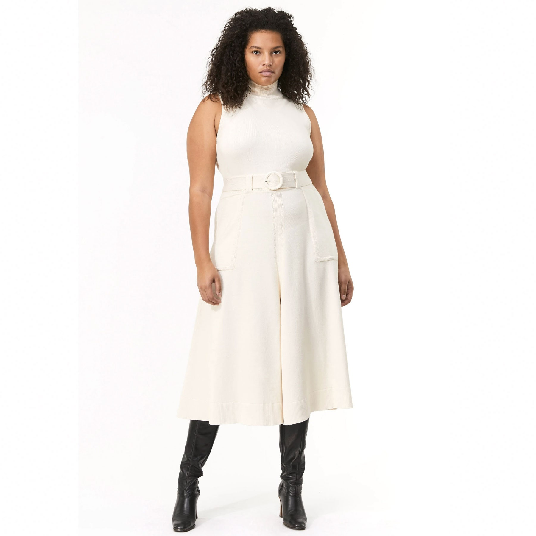 model wearing white turtleneck dress with high black boots
