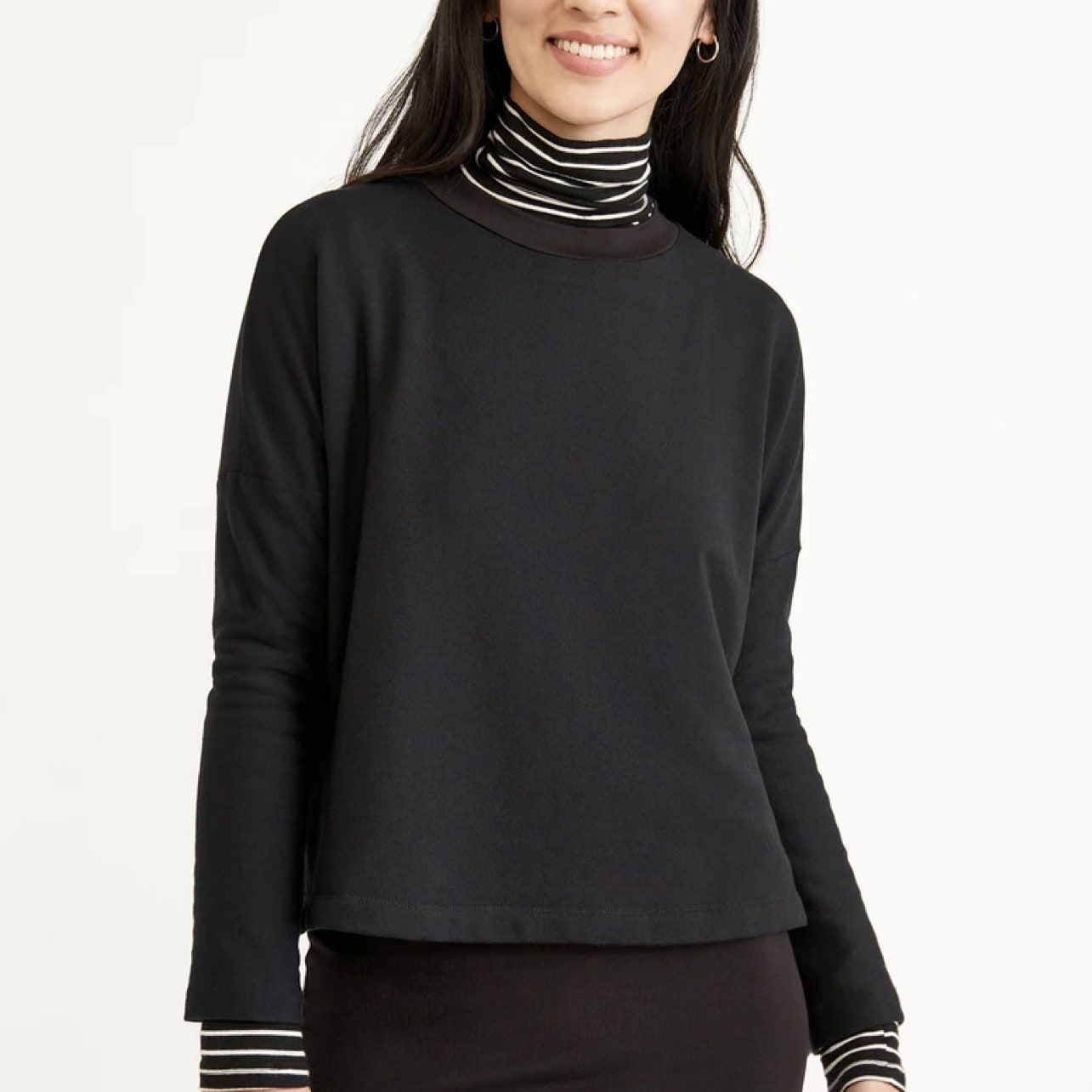 model wearing black sweater with black and white striped turtleneck underneath