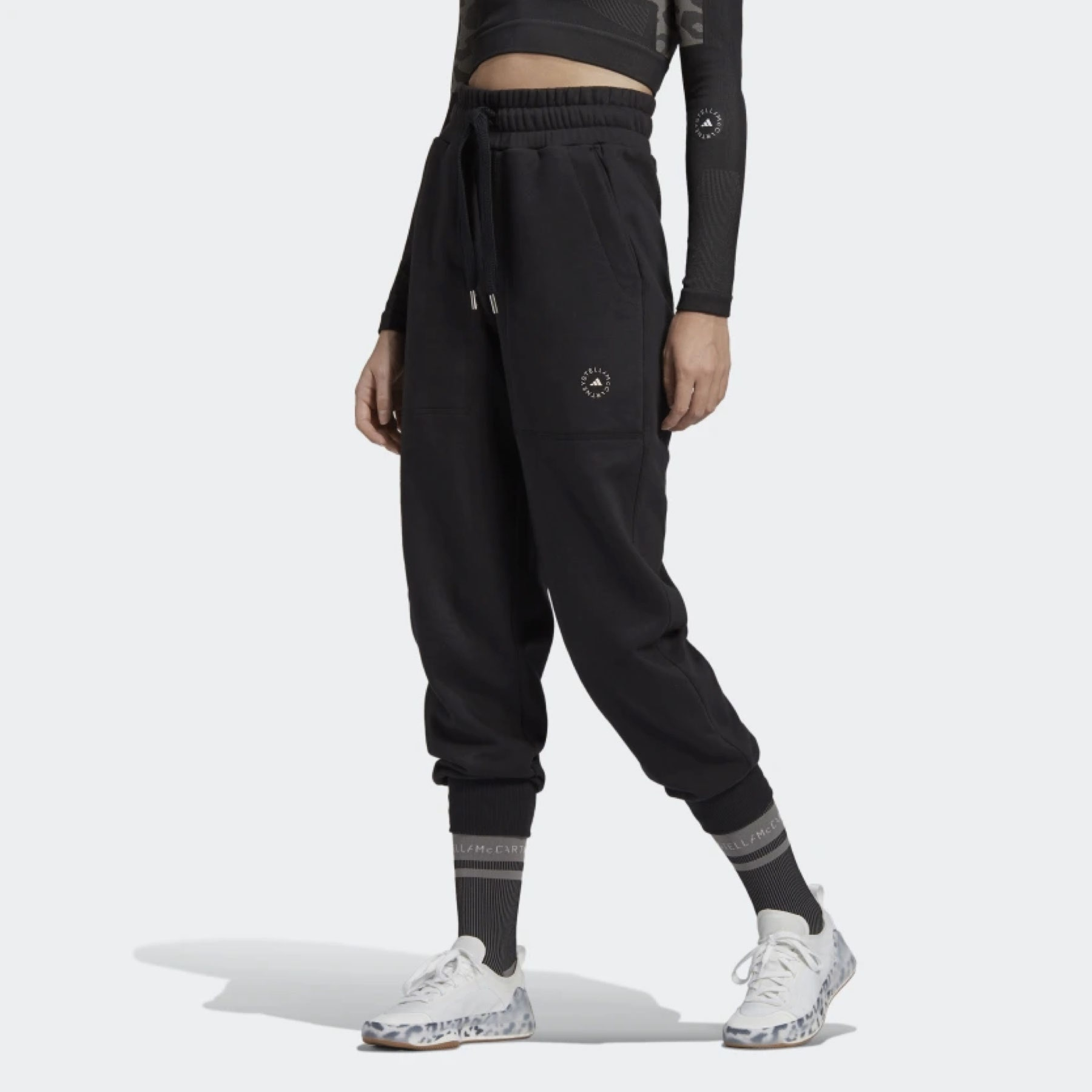 model wearing black sweatpants and white sneakers
