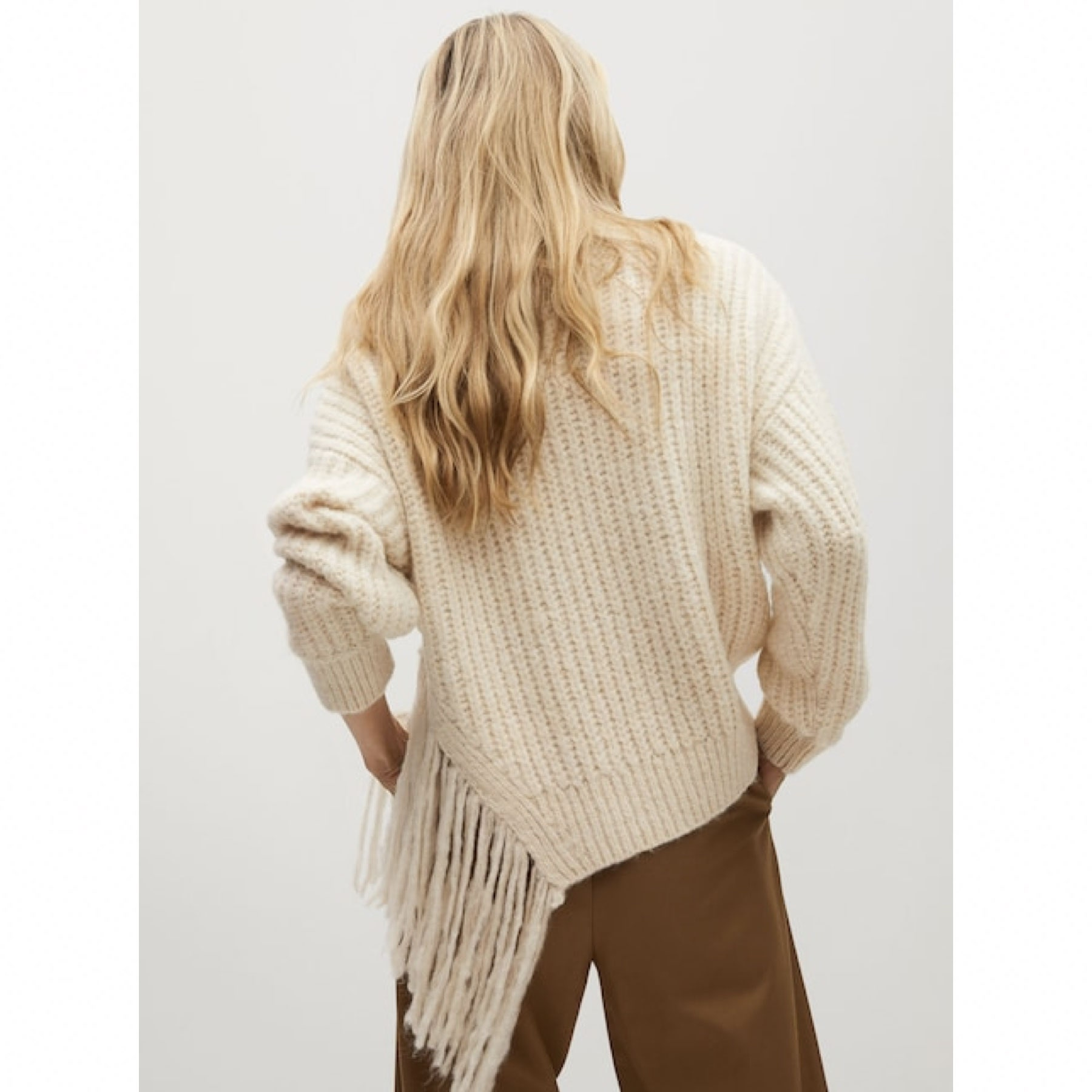model wearing white ribbed sweater with fringe in the back