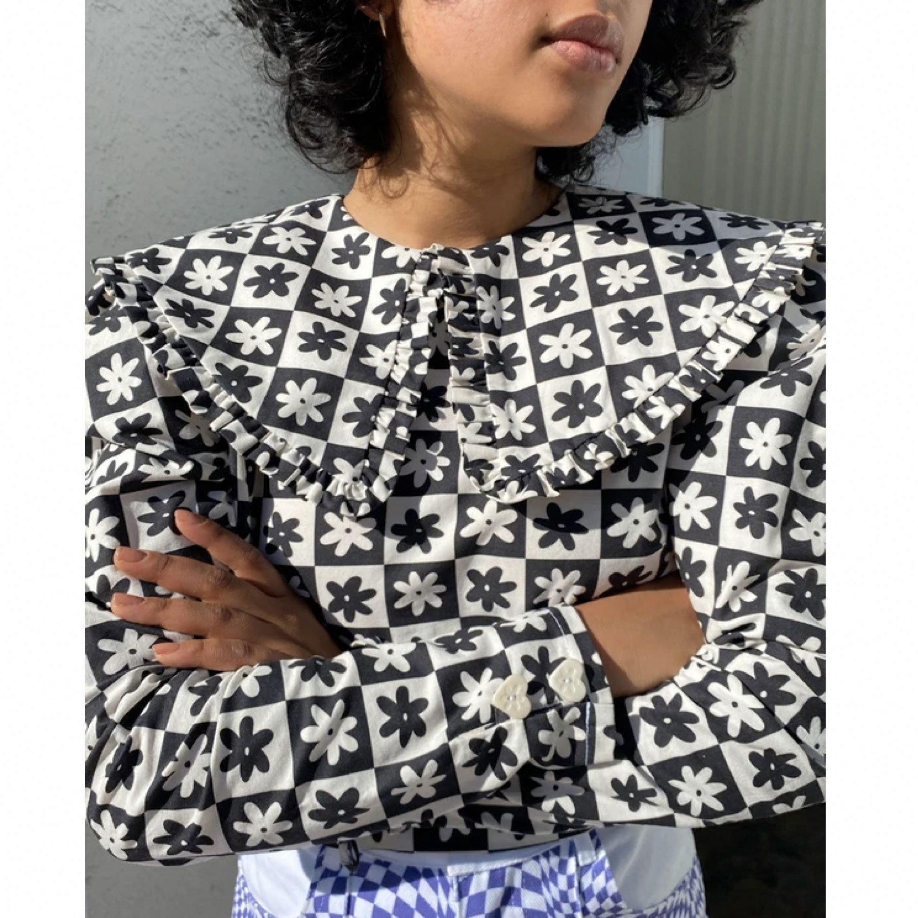 model wearing black and white floral top with large collar