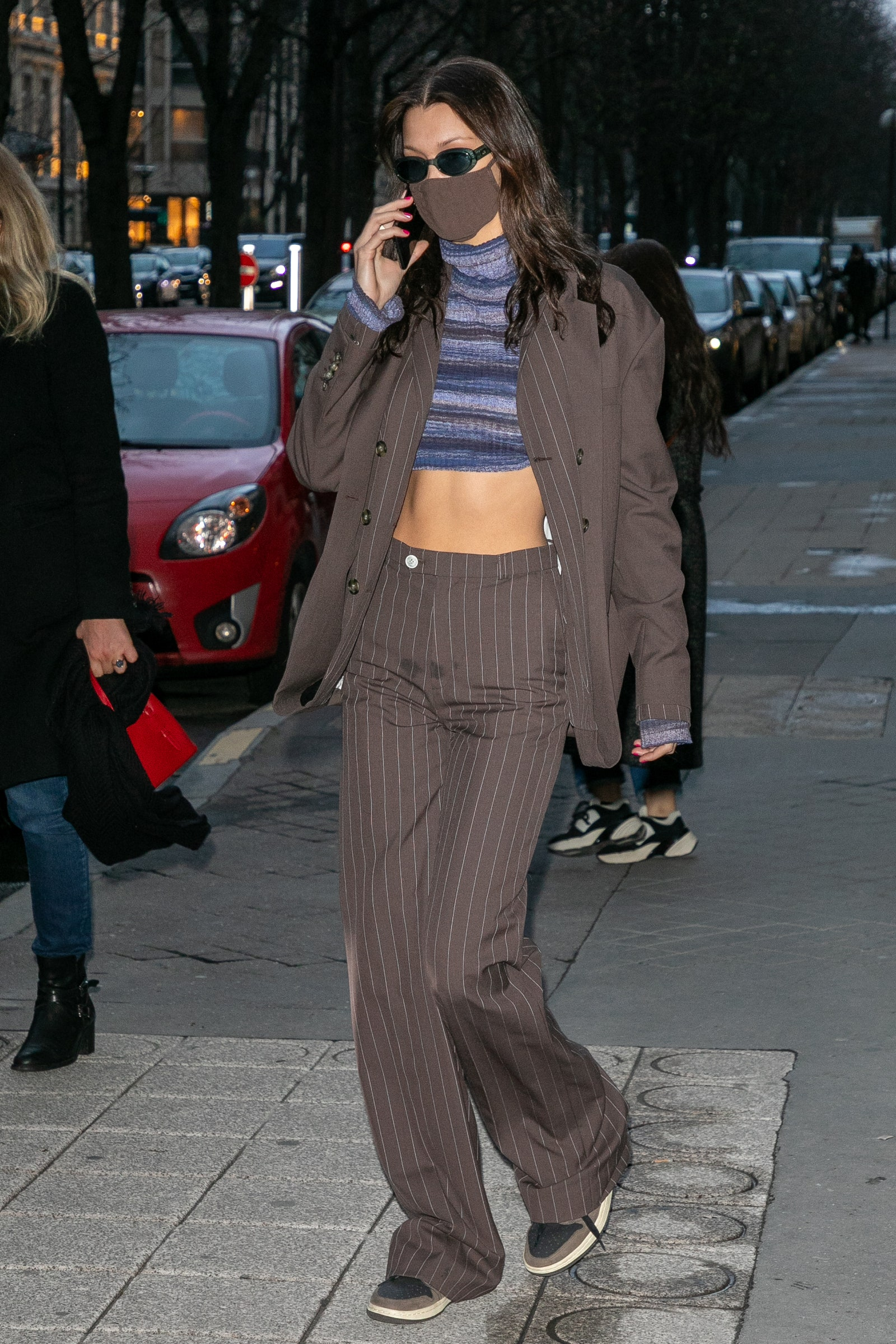 pBella Hadid's hint of untied shoelace really ties the puddle trouser set together.p